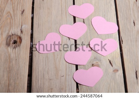 Pink paper Saint Valentines hearts on rough barn wood texture background - stock photo
