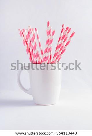 Pink paper straws in white mug - stock photo