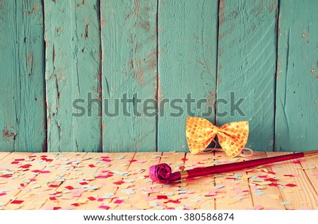 pink party whistle on wooden table with colorful confetti. vintage filtered image  - stock photo