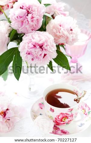 Pink peonies in vase and cup of tea - stock photo