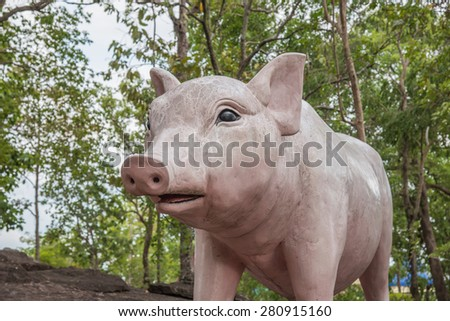 Pink pig statue on stone - stock photo