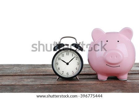 Pink piggy bank and clock on white background - stock photo