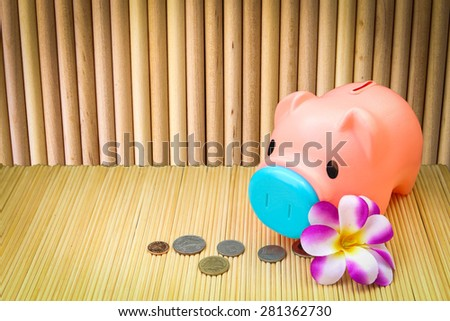 pink piggy bank and coin on round wooden wall background - stock photo