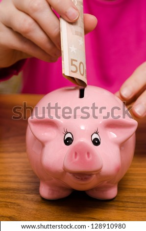 Pink piggy bank and fifty euro note - stock photo