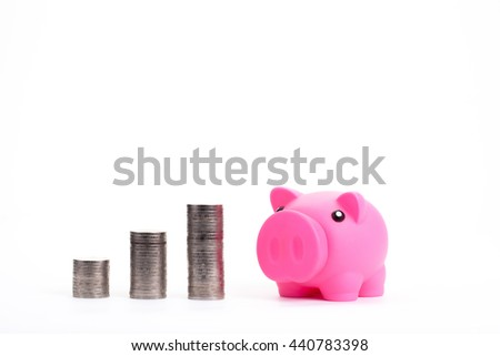 Pink piggy bank and silver coin tower on white background