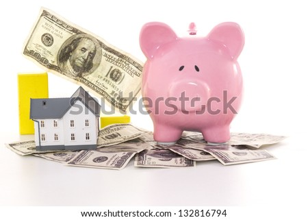 Pink piggy bank beside miniature house and graph on white background