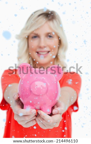 Pink piggy bank held by a smiling attractive woman against snow falling - stock photo