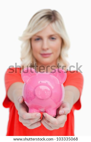 Pink piggy bank held by a teenage girl against a white background - stock photo