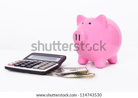 Pink piggy bank near calculator and one hundred dollar bills, isolated on white background.