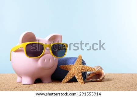 Pink piggy bank on a beach with sunglasses, travel savings concept. - stock photo