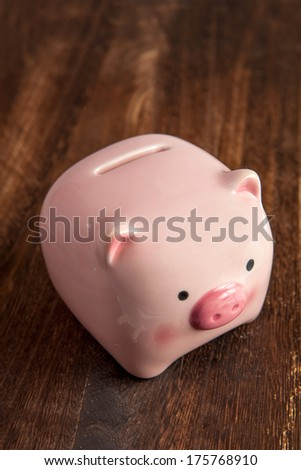 Pink piggy bank on a wooden brown table - stock photo