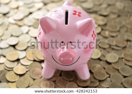 pink piggy bank on coins background