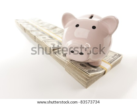 Pink Piggy Bank on Row of Hundreds of Dollars Stacks Isolated on a Gradated Background. - stock photo