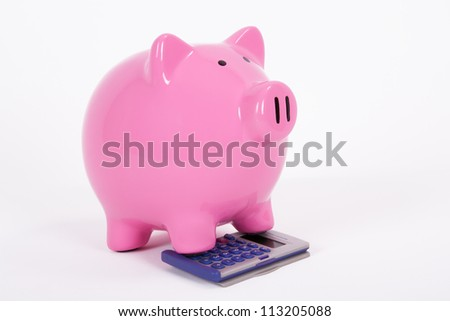 Pink piggy bank on the calculator, isolated on white background. - stock photo