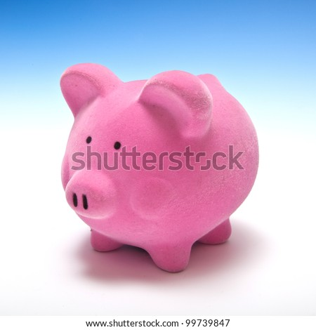Pink piggy bank or money box on a graduated blue studio background.