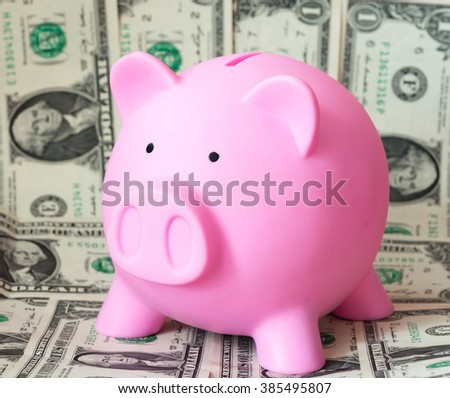 pink piggy bank over dollars