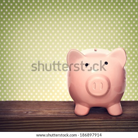 Pink piggy bank over green polka dots background - stock photo