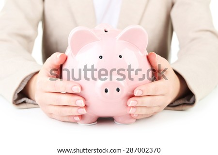 Pink piggy bank protected by hands