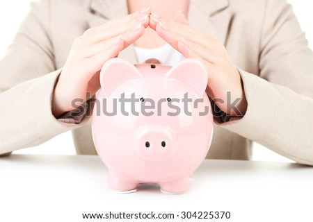 Pink piggy bank protected by hands, making roof