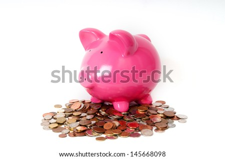 Pink Piggy bank sitting on coins  - stock photo