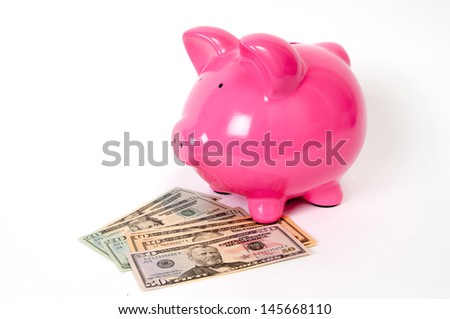 Pink Piggy bank sitting on coins with USD american bank notes coming out the top.
