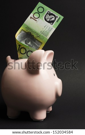 Pink Piggy Bank with Australian money against a black background, for savings concept, with 100 dollar note. Vertical. - stock photo