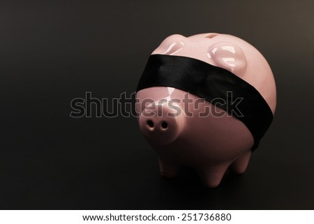 Pink piggy bank with black blindfold standing on black background - horizontal - stock photo