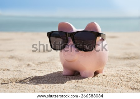 Pink Piggy Bank With Black Sunglasses On Beach - stock photo