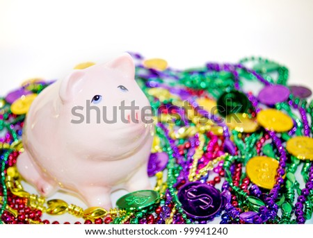 Pink piggy bank with colorful Mardi Gras beads and coins - stock photo