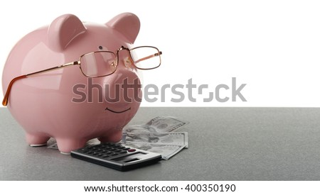 Pink piggy bank with dollar banknotes, glasses and calculator on white background - stock photo