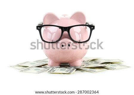 Pink piggy bank with glasses on dollars isolated on a white - stock photo