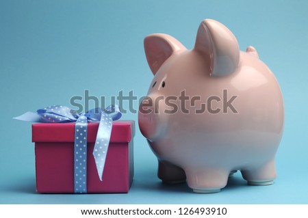 Pink Piggy Bank with pretty pink gift and blue polka dot ribbon bow against a blue background. - stock photo