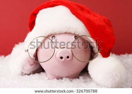Pink piggy bank with Santa hat with pompom and glasses standing on white snow on red background - stock photo