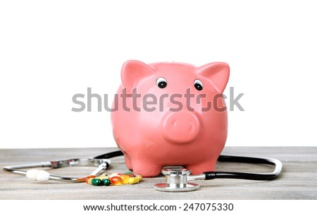 Pink piggy bank with stethoscope on white background - stock photo