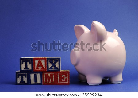Pink piggy bank with Tax Time message on building blocks for Tax Day or End of Financial Year financial returns or retail stock-take sales. - stock photo