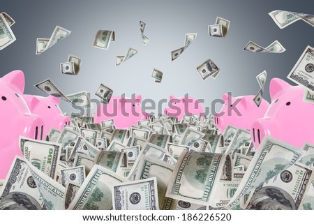 Pink piggy banks in one hundred dollar money farm and banknotes falling on dark background. - stock photo