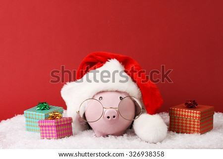 Pink piggy box with glasses and santa hat with pompom and three gift boxes with ribbon standing on white snow on red background - stock photo