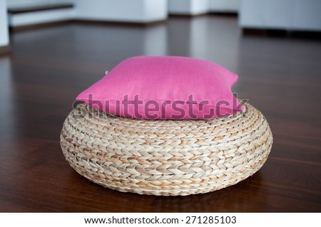 Pink pillow on pouffe in white interior