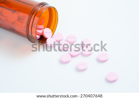 Pink pills an pill bottle on white background - stock photo