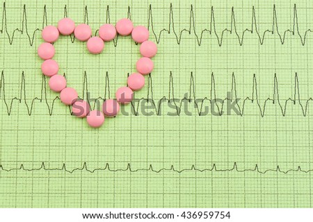 Pink pills forming a heart shape on green paper of EKG(Electrocardiogram). - stock photo