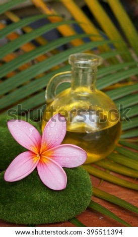 Pink plumeria flower and aromatic massage oil - stock photo