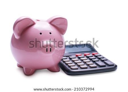 Pink porcelain piggy bank near a desk calculator, concept of financial operations and profit, close-up with shadow on white