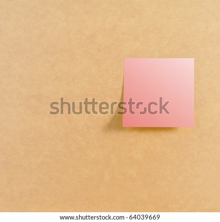 Pink post it on right of brown board texture - stock photo