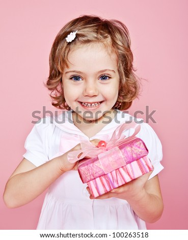 Pink present box in hands of a happy girl - stock photo
