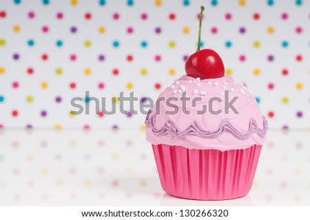 pink princess cupcake with cherry on top on a dotted background. birthday card design. - stock photo