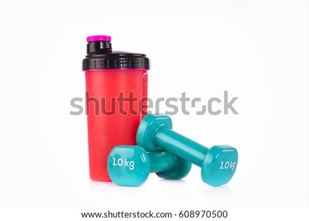 Pink protein blender bottle with a pair of blue fitness dumbbells. Fitness studio concept.
