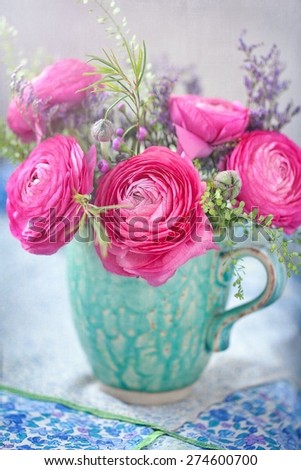 Pink ranunculus flowers close-up in a ceramic jug  on the table. - stock photo