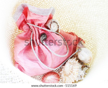 pink raw-silk bag with shells against straw textured cloth