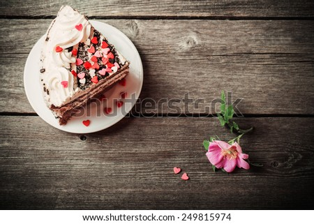 pink rose and cake on wooden background - stock photo
