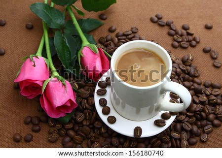 Pink rose black coffee cup and coffee beans on cork board - stock photo